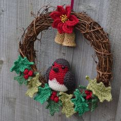 Crochet Christmas Wreath with Robin, Poinsettia, Holly and Bells that really 'ding'! Made by me, Victoria Williams, using attic24 holly/berries pattern, robin pattern from Etsy and bell pattern from Ravelry.
