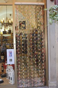 Wine Cork Curtain - (drill a thin hole thru each cork very slowly; string nylon thru, tying a knot after each cork, adding beads or charms inbetween corks)