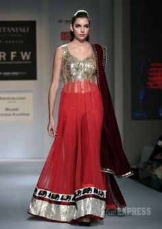 A model takes to the ramp in a rich red and gold Archana Kochar creation. #Fashion #Style #Beauty
