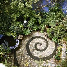Pebbles of the same size, but different colors, create a spiral focal point in this bite-size garden. | Photo: Red Cover/Alamy | thisoldhouse.com