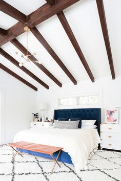 white bungalow bedroom with dark wood beams, navy tufted headboard, royal blue velvet bed base, white nightstand with brass details, terra cotta leather bench, white trellis shag rug, brass modern chandelier, pantone lapis blue