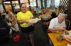 Long-time server Merry Futch brings food to a table at J. Michael's Philly Deli in 2014. StarNews file