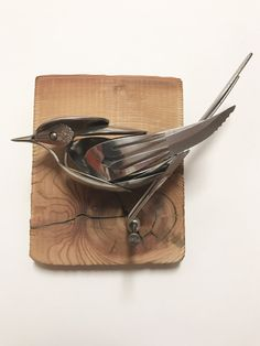 Bird made from upcycled utensils and scrap metal mounted on reclaimed wood.
