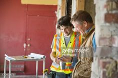 Stock Photo : Foreman and tradesman looking at mobile phone at construction site