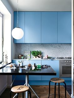 The sink and faucet—notice their reflection in the glass—are by Mora Armatur. Resident Saša Antić purchased the stool from local vintage shop Dusty Deco. A retro Ikea pendant lamp hangs above the kitchen table, which is an architect's drafting board Antić found at Grandpa, another store in his neighborhood. Photo by: Jonas Ingerstedt