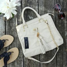 "Knick Knack Satchel Tassel Bag Olivia + Joy brand. Knick Knack Satchel. 13"" W x 10"" H x 5"" D Double Handles - 4.5"" drop Chain-link shoulder strap - 14.5"" drop. Top zip closure. Roomy interior with zip pocket and 2 slip pockets. Cream color pebbled faux leather exterior. Snap pocket on the front. Zip pocket on back. Gold-tone hardware and accent stitching along with over-sized tassels decorated with bamboo beads, give this classic satchel a unique look. Harly visible tiny discolored spot on…"