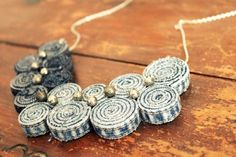 Recycled, geometric necklace made of vintage jean pants and embellished with little metal balls. Backside is covered with ivory lace.