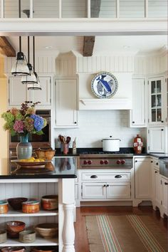 Country chic kitchen, all white with colorful crockery.....loving the beadboard above the cabinets!