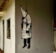 Banksy heeft Louisiana in Amerika verlaten met een kunstwerk waarbij veel commotie is ontstaan. Je ziet een lid van de KKK (Ku Kux Klan) die is opgehangen.