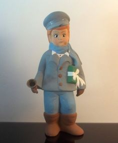 Vintage Christmas Caroler Chris 13 inches Sugarplum Collection  Beautiful Bisque Christmas Caroler  From the Sugarplum Collection  This older boy wears a blue coat over blue pants and brown boots. In his right hand, he carries a large brass bell and a green gift box under his left arm.