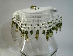 Cobre fruteiras com tecido em organza de 35 cm bordado com pedras acrílicas e miçangas de cristal verde oliva. O bordado mede mais cerca de 6 cm.    Acima de 3 unidades, ganhe desconto de 5%.
