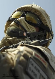 A soldier from 1 Squadron, Royal Air Force Regiment on patrol around Kandahar Air Field, Southern Afghanistan shields his face from an impending sand storm.