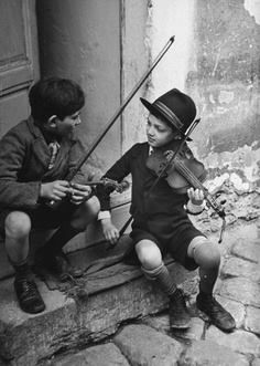 Gypsy children playing violin in street, Budapest, Hungary, 1939