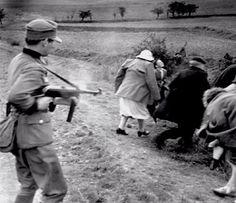 German soldier machine-gunning a group of civilians.