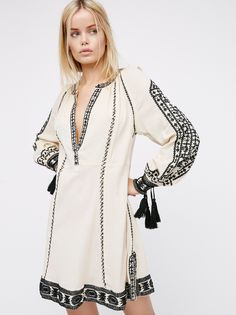 New Romantics Magnolia Dress   Beautiful bohemian dress with a relaxed vibe. Features eye-catching embroidery and glimmering mirror accents throughout. V-neckline. Tassels on the open sleeve cuffs. Subtle side vents. Comfortable cotton fabrication with an easy shape.