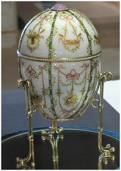 Imperial Gatchina Palace Egg – Fabergé, 1901; workmaster, Mikhail Perkhin; crafted from gold, opalescent white enamel, silver-gilt, portrait diamonds, rock crystal, and seed pearls; 4 15/16 x 3 9/16 in. (12.5 x 9.1 cm); the egg opens to reveal the surprise a scaled model gold replica of the palace at Gatchina, the Dowager Empress's principal winter residence outside Saint Petersburg. Nicholas II presented it to his mother, the Dowager Empress Maria Feodorovna, on Easter 1901. .