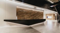 Visitors check in at an angular, black reception desk. Behind it, an accent wall is faced with slanted wooden boards. Offices for member services are housed within glass-walled rooms that are meant to feel highly accessible. Black Reception Desk, Reception Desk Design, Lobby Reception, Office Reception, Gym Interior, Lobby Interior, Interior Design Studio, Retail Interior, Interior Walls