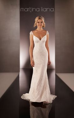 Martina Liana featuring a cap sleeve wedding dress with a low V-front and back and crystal embellishments throughout with a that skirt flows into a sweep train.