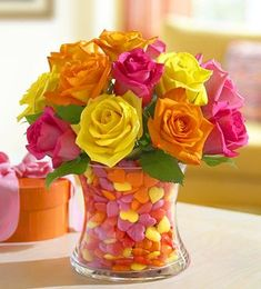 Picture of colorrful roses arrangement with glass vase full of sweet treat.JPG
