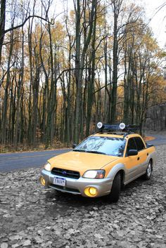 yellow subaru baja with blacked out grill and roof rack with lights