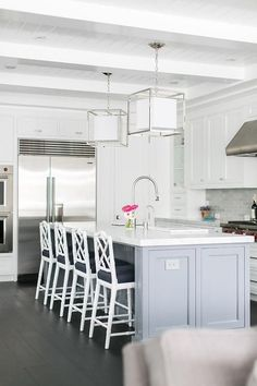 Caged Medium Lanterns hang over a gray island topped with a white marble countertop seating four white bamboo counter stools with black seat cushions on dark walnut stained wood floors facing an island sink with an oversize polished nickel gooseneck faucet.