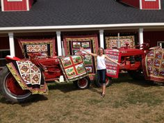 Quilts displayed on tractors in front of the barn. Plus, you can buy the fabric and patterns here too.