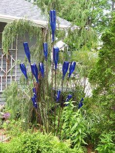 gartendeko-selber-machen-guenstig-glasflaschen-blau-sahl-staebe-pflanzen-boden