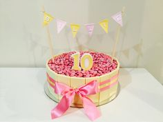 Pink M & M cake with white chocolate edging. A pretty bunting added to complete the look