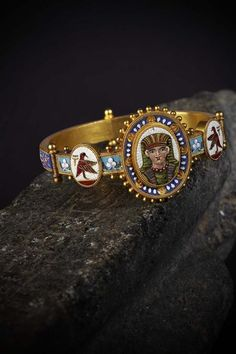 19TH CENTURY GILT AND MICROMOSAIC SET EGYPTIAN REVIVAL BANGLE  apparently unmarked, of hinged form, the central panel of an Egyptian queen, ball edged border, with band decorated birds and hieroglyphs and flowers with doves of peace to the rear hinged panels all with rope twist borders