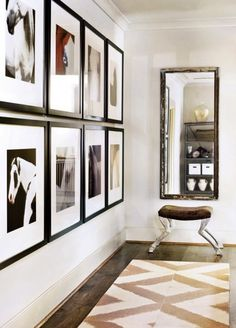 hallway lined with pictures and ending with a mirror