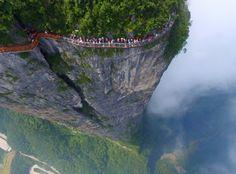 People walk on a sightseeing platform in Zhangjiajie, Hunan Province, China.  Zhangjiajie, Provinz Hunan, China, von Reuters, publiziert am 2. August  In buchstäblich schwindelerregender Höhe tasten sich Besucher eines Skywalks an einer Felswand in der chinesischen Provinz Hunan voran. Die Sandsteinpfeiler in dem Gebiet Wulingyuan sind eine bekannnte touristische Sehenswürdigkeit und reichen bis zu 200 Meter über dem Erdboden.