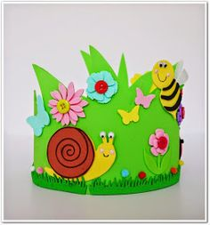 Esta corona ha sido un encargo de una amiga para el centro infantil donde asiste su hijo. La base en goma eva verde, las flores y mariposa...