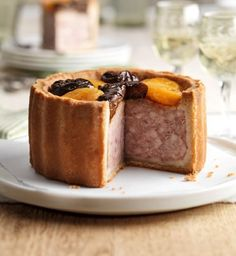 An uncured British pork pie with a golden hot-water crust pastry is decorated with plump dried apricots and prunes for a decadent taste.