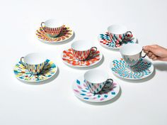 A mirrored cup that gets its striking patterns and colors by reflecting the saucer below.