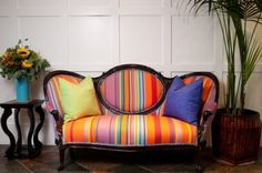 Striped modern fabric on a curvy, old-fashioned settee. This beauty would feel at home in a variety of settings: modern Mexico, eclectic bohemian, spare white or cozy B.