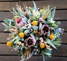 A gorgeous large rustic wedding bouquet featuring artificial burgundy proteas, yellow billy buttons,