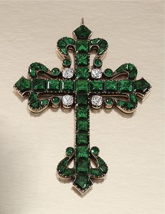 A Latin cross, each cardinal point terminating in a stylised Fleur-de-Lys, set with foil backed table-cut paste of green tint accented by similarly-set circular-cut paste of near-colourless tint, late 18th century