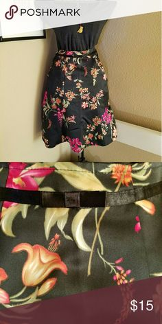 "Floral Satin Swing Skirt Flirty swing skirt in lovely floral on black satin with ribbon waist detail. EUC Size M but the waist has been professionally tailored to 28"", stiching could be easily removed to return it to a true medium. Notations Skirts Circle & Skater"