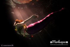 Underwater photograph of mermaid Ondine of the Merlesque mermaids, swimming up towards a beam of light in the water, in a pink and purple tail. Find out more about the Merlesque mermaids at: http://www.realmermaids.co.uk, or follow them on Facebook at: http://www.facebook.com/RealMermaidsUK