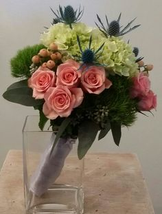Bridesmaid bouquet with peach spray roses,  green tric,  thistle, etc