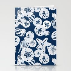 Pretty white sea shells and sand dollars on a navy blue background.<br/> <br/> ocean, nautical, beach, sea...