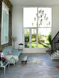 Interesting elements: the beautiful window/door wall; room scale, the floral fabric; huge chandelier; massive mirror; pickled floor. The combination of these manages to be vintage and modern at the same time.