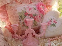 Seats covered in lace pillows, ribbons and pearl strands with pink candelabras around the room