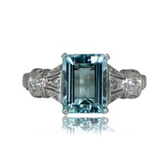 A beautiful vintage aquamarine ring, adorned with diamonds along the shoulders, and highlighting a stunning emerald-cut aquamarine. The center stone is prong-set in each corner and sits flush against the accenting handcrafted platinum work.The aquamarine is very lively and weighs approximately 2.10 carats. This vintage ring was handcrafted during the Art Deco Era, circa 1930.