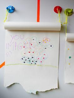 Vista de un rollo de papel de dibujo MALA fijado a una pared con unos ganchos de pared KROKIG de colores.