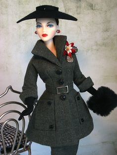 Actress Gene Marshall wears the drama of a wool OOAK, belted, peplum jacket accented with over-sized pockets and button detailing from The Couture Touch. A wing collar and 3/4 length cuffed sleeves complete this chic ensemble. Muff from Mattel. J'Adore Gene Marshall wears her original black felt hat that has been restyled.