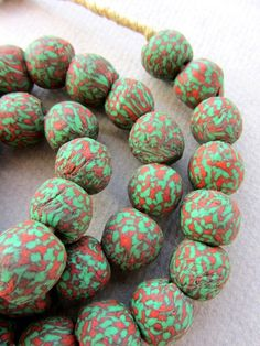 A beautiful strand of about 43 glass Krobo beads from Ghana on raffia 24 inches long. Each handmade bead measures approximately 13mm x 14mm. The hole is