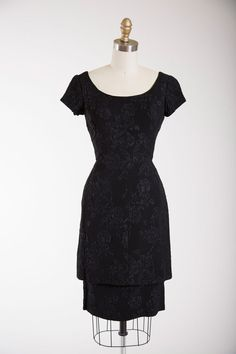 """1950s vintage dress made of a black acetate crepe. Fitted waist, wide scooped neckline, short capped sleeves and darted bust. Straight skirt and overskirt. Long back metal zipper.  ☞ Measurements Bust: 33 Waist: 24 Hips: 36 Length: 38"""" plus 2.5"""" hem allowance Label: Lord + Taylor  Made of a medium acetate crepe. Excellent vintage condition. Presents and wears beautifully. Freshly dry cleaned and ready to wear.  ☞ visit the shop http://www.etsy.com/shop/stutterinmama  website…"""