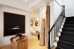Apartment entryway with large art work,  a wooden oval table, and elegant stairs