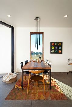 here the dining table and window work together (it's as if the table dropped down from the wall, like an ironing board) to frame a view perpendicular to the large view through the sliding glass door.